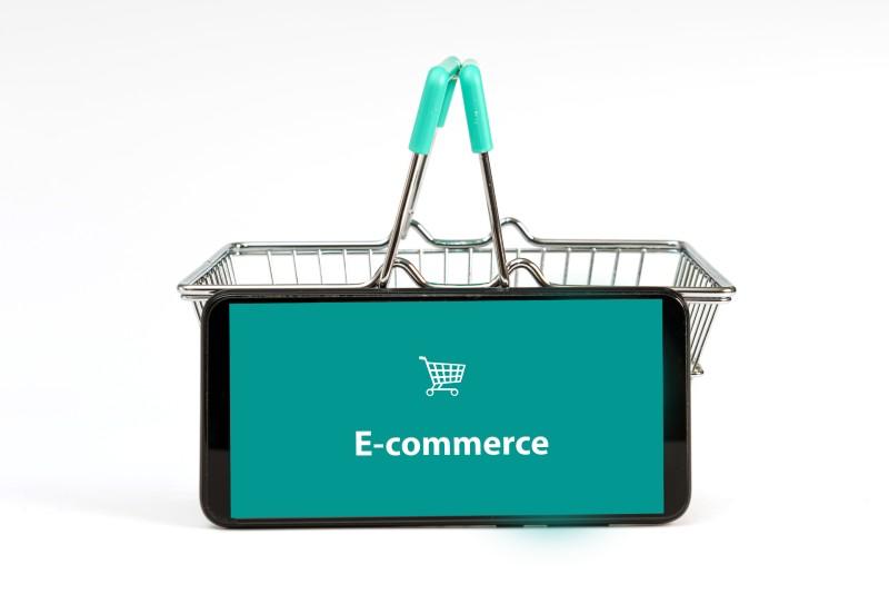 """Telefono con scritta """"e-commerce"""" e cestino spesa - aprire un ecommerce nel futuro post-pandemia - Web Agency Perugia The Brick House"""